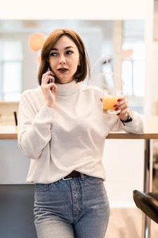 Молодая нежная леди в белой футболке и синих джинсах на кухне разговаривает по телефону
