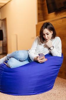 優しい女性が彼女の友人とのテキストメッセージに彼女の電話を使用して明るい紫のバッグの椅子に座っています。