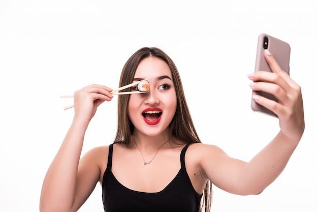 Удивленная улыбающаяся азиатка закрывает глаза суши-роллом и делает селфи на своем телефоне