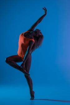 エクササイズ、芸術体操の要素を実行する、ジャンプ、空気中の分割飛躍を行う青いスポーツウェアドレスで美しいクールな若いフィット体操選手女性