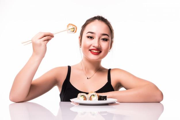 Счастливый довольно азиатский взгляд со скромной прической сидеть на столе есть суши роллы улыбаясь, изолированных на белом