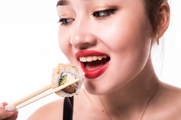 Закрыть портрет красивой женщины едят суши роллы