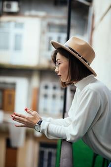 バルコニーに滞在している短い髪と帽子の若い