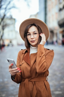 スマートフォンの秋のストリートでワイドハットテキストメッセージの若い