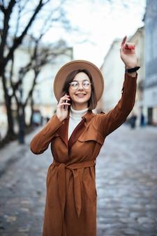 暖かい秋の日に通りを歩いて美しい若い女性