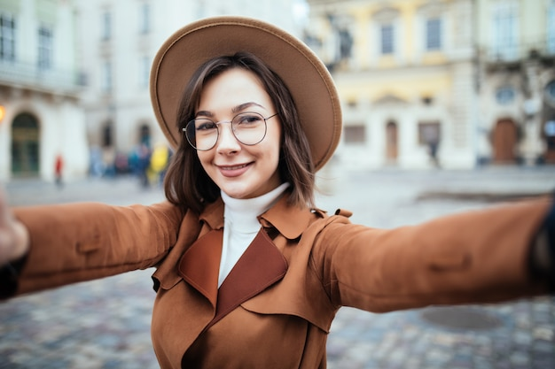 Красивая женщина в очках принимает селфи, держа ее телефон в городе