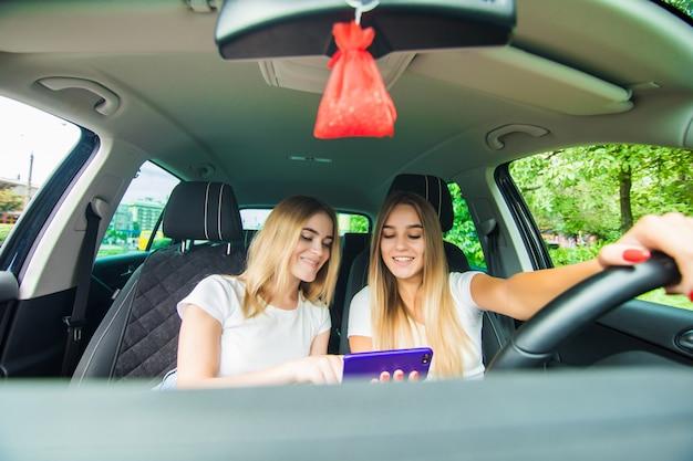 Две девушки с помощью телефона смотрят что-то в социальной сети, когда едут на машине по улице города.