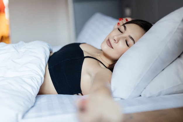 ベッドで横になっているセクシーな若い女性と彼女の腕を伸ばす