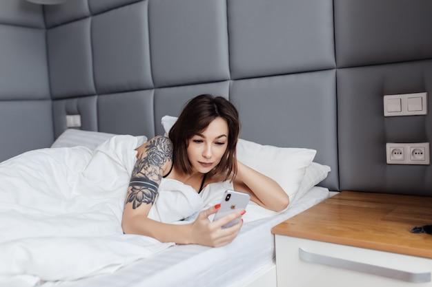 幸せな若い女は朝のベッドで目を覚まし横になっているスマートフォンを保持します
