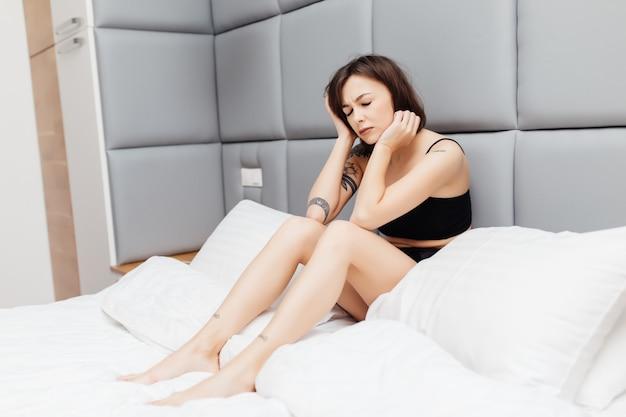 不幸な疲れブルネットの女性が彼女のベッドで朝目を覚ます