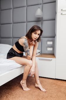 セクシーなパジャマの女性は彼女の明るい部屋でベッドの端に座る