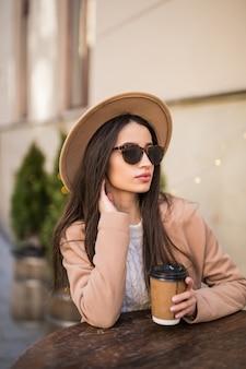 Молодая модница сидит на столе в кафе, одевается в повседневную одежду, темные очки с кофейной чашкой