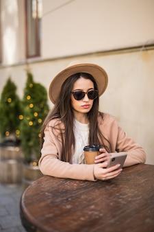 Молодая фотомодель сидит на столе в кафе, одевается в повседневную одежду, темные очки с кофейной чашкой и телефоном