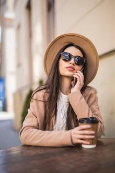 Мечтательная фотомодель сидит на столе в кафе, одевается в повседневную одежду, темные очки с кофейной чашкой