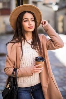 Молодая красивая дама, прогуливаясь по улице с сумочкой и чашкой кофе.