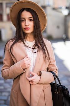 Молодая красивая красотка, прогуливаясь по улице, одета в повседневную осеннюю одежду, яркое пальто