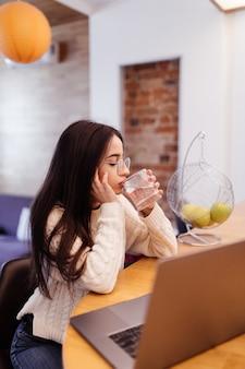 金髪の黒い髪のきれいな女性は彼女のラップトップに取り組んでおり、キッチンで水を飲む