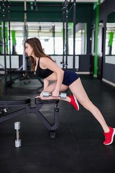 Сексуальная мускулистая женщина работает с двумя гантелями