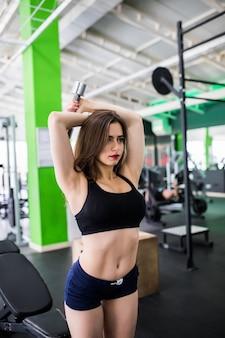 メタリックダンベルのあるモダンな黒のスポーツウェアに身を包んだ女性は、スポーツクラブで毎日トレーニングをしています