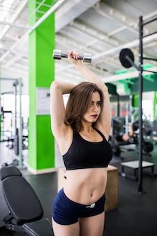 金属製のダンベルを持つかなり若い女性はスポーツクラブで彼女の毎日のトレーニングを行います