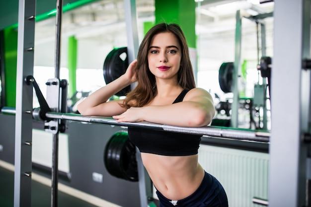 タイトなスポーツウェアの強い女性がスポーツクラブでポーズをとってください。