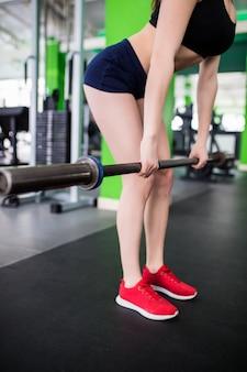 スポーツクラブのファッションスポーツウェアで着飾ったバーベルを持つかなりスポーツの強い女性