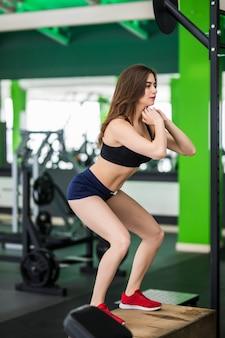 Женщина фитнеса с длинными волосами работает с спортивным тренажером коробки шага в спортзале фитнеса