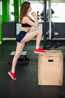 長い髪の優しい女性は、フィットネスジムでステップボックススポーツシミュレータを使用しています。
