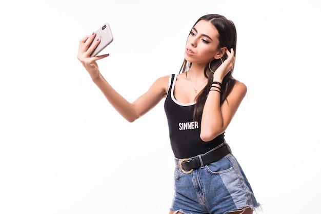Брюнетка вкратце делает селфи на своем телефоне изолированно