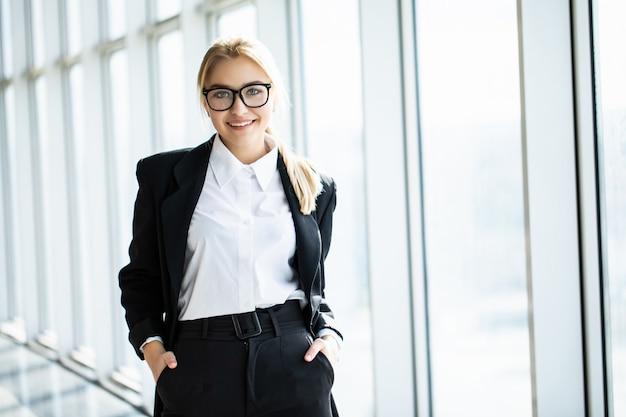 Молодая блондинка со скрещенными руками стоит в углу панорамного офиса.