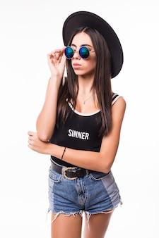 Привлекательная женщина в черной футболке джинсы шорты шляпу и солнцезащитные очки позирует.