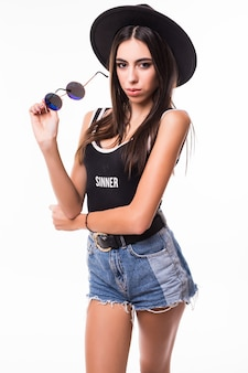 Красивая женщина в футболке шорты и солнцезащитные очки позирует.