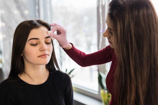 Искусный визажист делает макияж бровей для молодой женщины с темными волосами