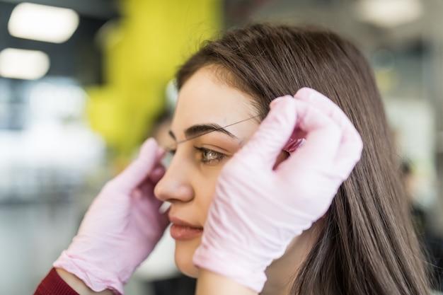Мастер аккуратно делает процедуру брови для симпатичной женской модели