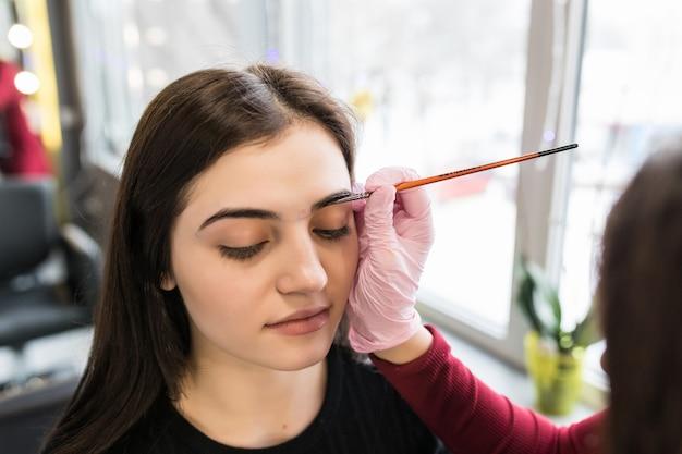 女性マスターがメイクアップ手順中に美容サロンに眉ペンキを置く