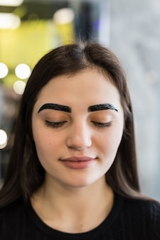 Красивая модель с промежуточным результатом процедуры макияжа