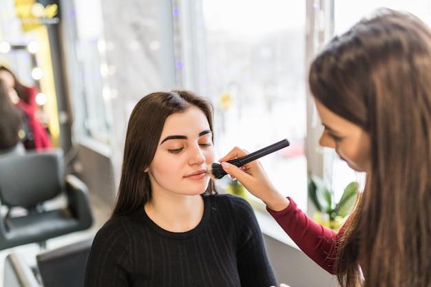 Красивая молодая женщина с длинными каштановыми волосами делает яркий макияж