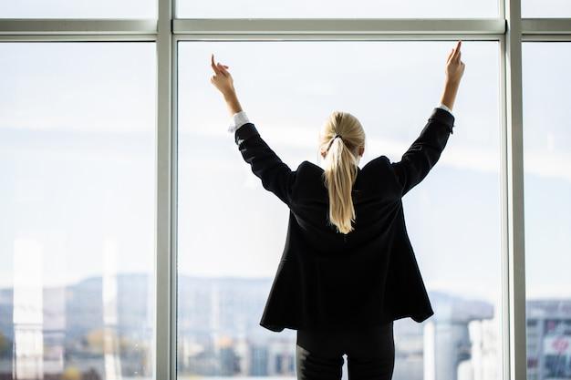 自信を持って女性実業家のオフィスの窓に立って手を広げて、大都市を楽しんで、成功した起業家が両手を広げてビジネスの成功を祝って、強力なインスピレーションを受けた、背面図
