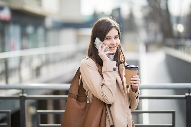 コーヒーカップと電話を保持している通りを歩いてカジュアルな服を着た女性