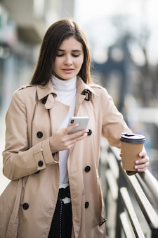 Улыбающаяся молодая женщина в светло-коричневом пальто читает новости по телефону снаружи