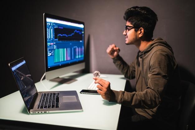 コンピューターモニターの財務グラフでオフィスで働いているビットトレーディングデータ分析概念をチェックするビットコインを持つインドのトレーダー