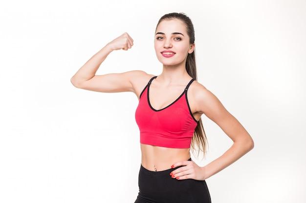 Портрет красивой женщины фитнеса показывая ее бицепс на белой стене