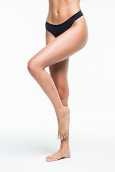 白い壁に分離されたランジェリー足で美しいスリムな女性の身体