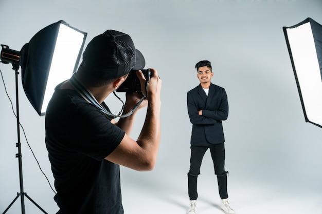 レイとスタジオでインドのモデルの写真を撮るプロの若い写真家