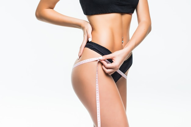 メーターテープで腰を測定する黒い下着の若い女性。