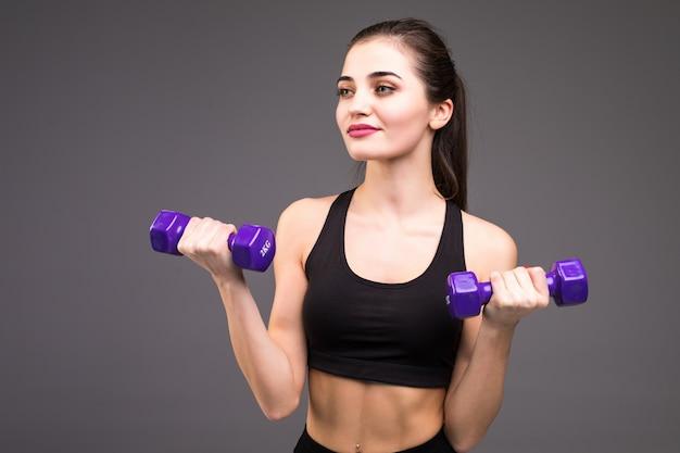 美しいフィットネス女性は灰色の壁にダンベルで運動の調子を整える