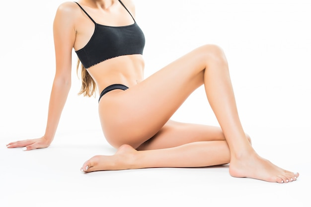 白い壁に分離された美しい女性の身体。床に座って足を手で触れる、美容とスキンケアのコンセプト。