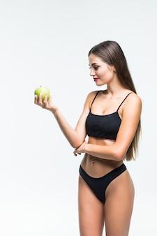 青リンゴを保持している若いスリムな女性。白い壁に分離されました。健康食品のコンセプトと過剰体重の管理。