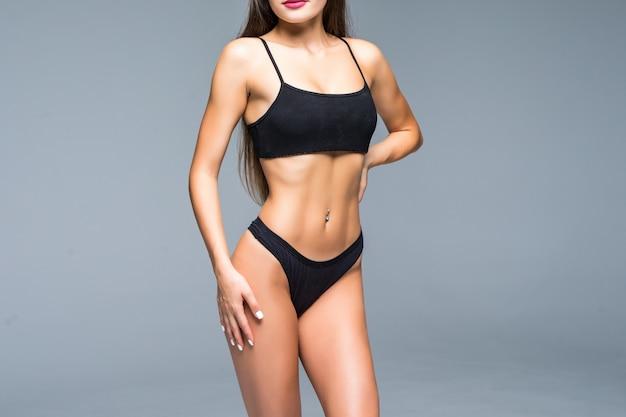 彼女のスリムな腹を指しているランジェリーの陽気な肯定的なセクシーなフィット女性。平らな胃、理想的な腰、彼女の体重について自慢している女性を示す女性。孤立した白い壁、フィットネス、スポーツ