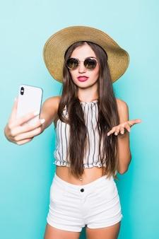 Портрет девушки мечты сделать селфи блог отправить воздушные поцелуи своим последователям онлайн-свидание, изолированных на бирюзовом фоне цвета